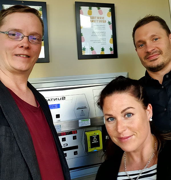 Installation completed. Customer Kirsi posing with suppliers Antti and Sami with Nayax Cashless Payment System.